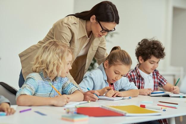 Excellentie vriendelijke jonge vrouwelijke leraar in glazen die haar kleine schoolkinderen in een klaslokaal helpt