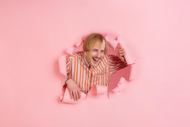 Excentriek lachend. vrolijke blanke jongeman vormt in gescheurd koraalpapier