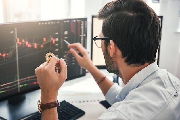 Exchange beurs achteraanzicht van jonge professionele handelaar in brillen wijzend op de gegevens