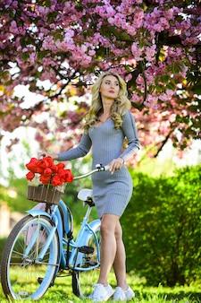 Excursie naar de tuin. meisje en sakura bloeien. fietstochten. kersenboom in bloei. atletische vrouw rijdt retro fiets. rust en reis. reis op de fiets. weekendconcept. lente vakantie. fietsen.