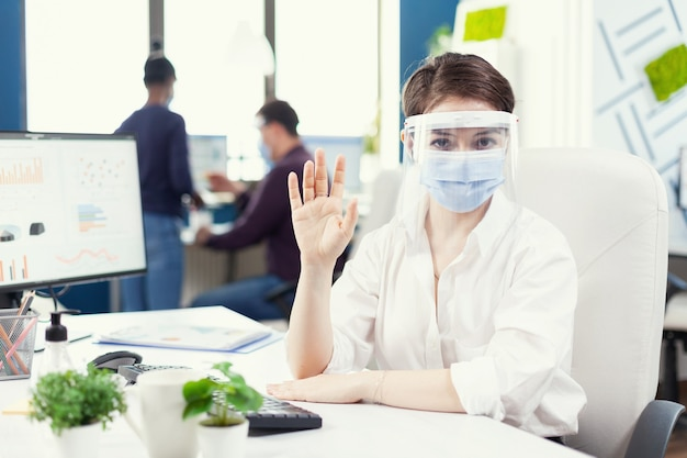 Executive draagt gezichtsmasker en beschermingsschild die met de klant communiceert tijdens covid-19..0 pov van manager die met het team op afstand spreekt tijdens online conferentie terwijl collega's die in de achtergrond werken