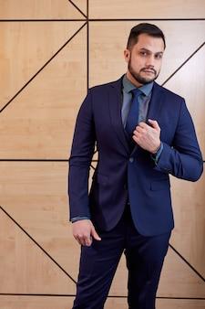 Executive in formele kleding poseren, na een ontmoeting met succesvolle mensen. kaukasisch mannetje staat camera vol vertrouwen te kijken. succes, zaken, elegantie concept