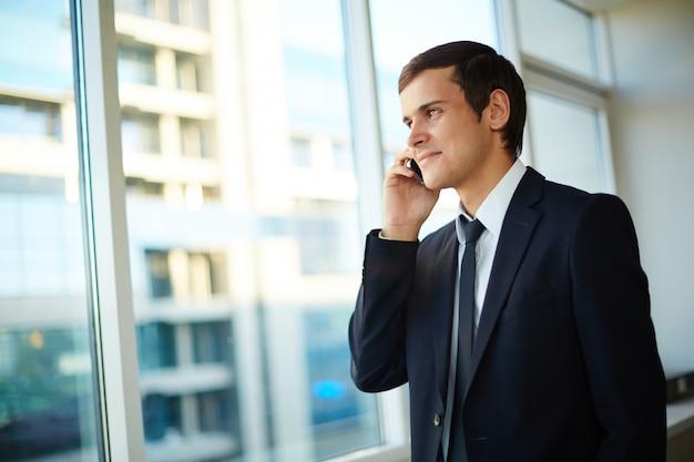 Executive kijken door het raam met de mobiele telefoon