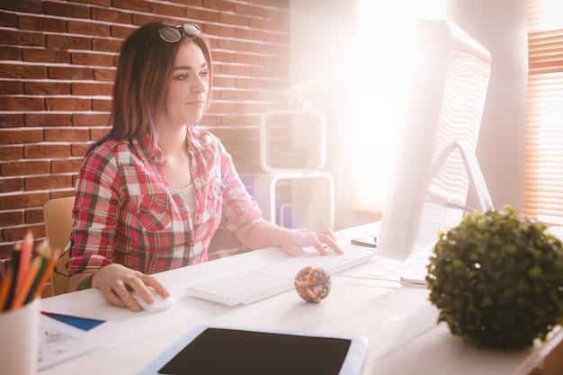 Executive met behulp van desktop computer op kantoor