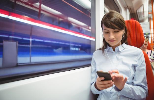 Executive met behulp van mobiele telefoon tijdens het luisteren naar muziek