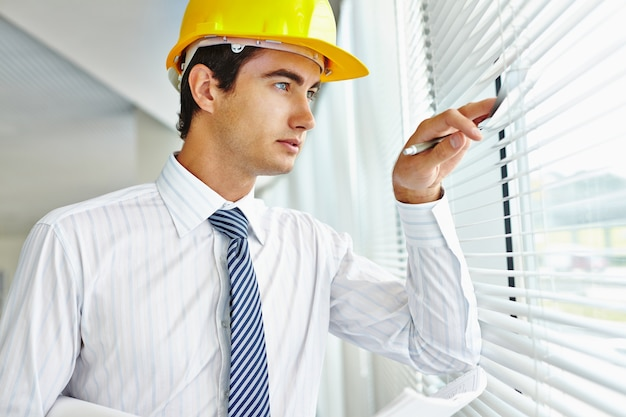 Executive met helm staren door het raam
