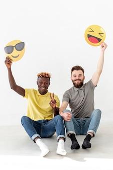 Exemplaar-ruimte mannelijke vrienden die op vloer zitten en emoji houden