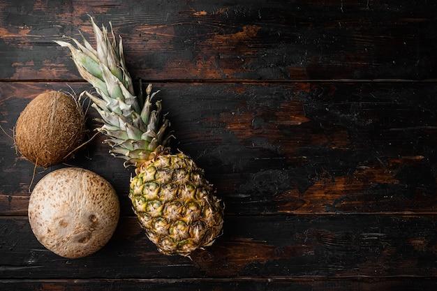 Exotisch fruit, ananas en kokosnoot set, op oude donkere houten tafel achtergrond, bovenaanzicht plat lag, met kopieerruimte voor tekst