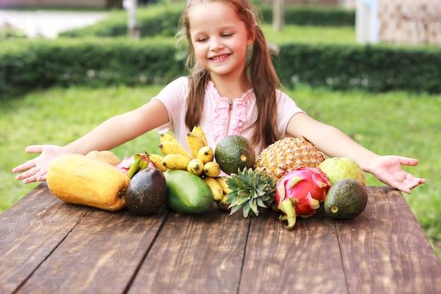 Exotisch fruit op houten tafel. zomer achtergrond met kleine lachende gelukkige meid