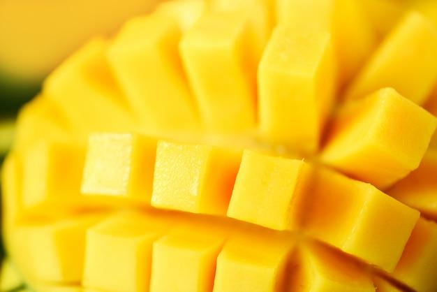 Exotisch mangofruit over tropische groene palmbladen op gele achtergrond. pop-artontwerp, creatief de zomerconcept.