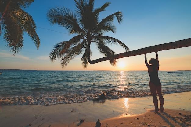 Exotisch tropisch strand. vrouw het ontspannen onder kokospalmvarenblad op toneel wit zandstrand. indonesië, kei-eilanden, molukken maluku, wab-strand