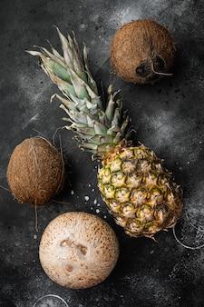 Exotisch vers fruit, ananas en kokosnoot set, op zwarte donkere stenen tafel achtergrond, bovenaanzicht plat lag