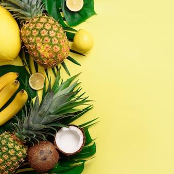 Exotische ananas, kokosnoten, banaan, meloen, citroen, palm en monsterabladeren op gele, violette achtergrond