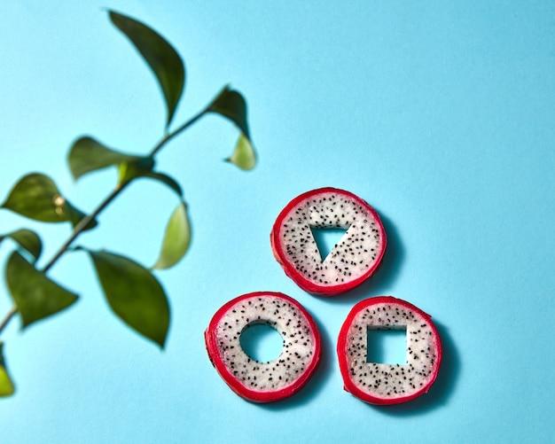 Exotische fruit pitahaya in de vorm van geometrische vormen en een tak van groene bladeren