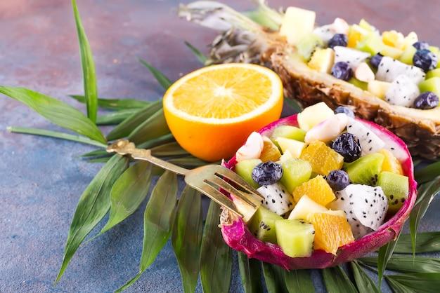 Exotische fruitsalade geserveerd in de helft van dragon fruit en ananas met palmtak op stenen achtergrond