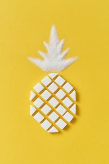 Exotische fruitsamenstelling creatieve ananas handgemaakt van rafined anf kristalsuiker zoete suiker op een gele muur met kopie ruimte. plat leggen.