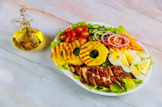 Exotische kleurrijke salade met groenten, kipfilet en gegrilde ananas