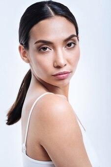Exotische schoonheid. het portret van een mooie donkerharige jonge vrouw in een wit hemdje terwijl ze half gedraaid tegen een witte muur staat