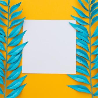 Exotische tropische bladeren en blanco papier op geel