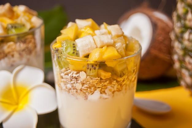 Exotische tropische fruitsalade met muesli en yoghurt in een glas met ananas en kokosnoot op de achtergrond.