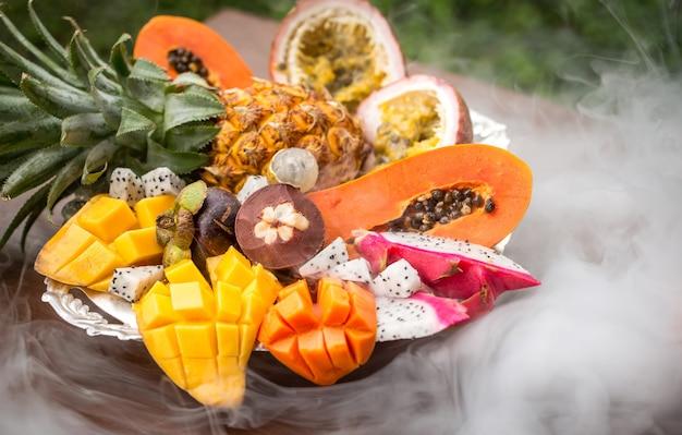 Exotische vruchten in rook van een close-up van een waterpijp op een dienblad Premium Foto