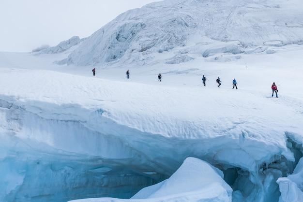 Expeditie van wandelaars in de besneeuwde steile bergen