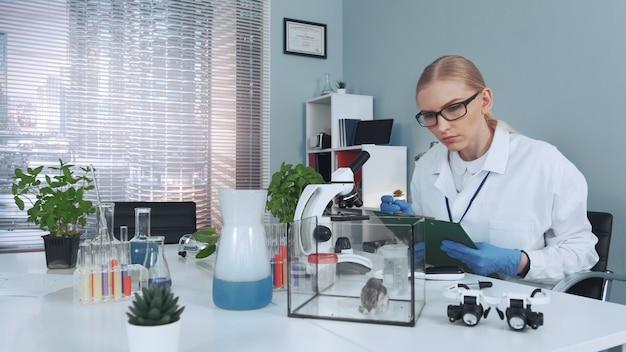 Experimenteren met hamster in een modern laboratorium: wetenschapper die diergedrag observeert en aantekeningen maakt