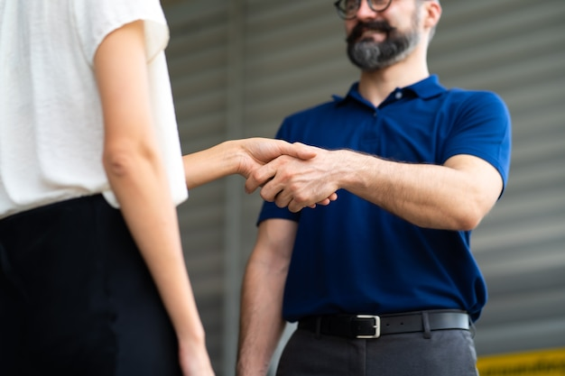 Expertise monteur handen schudden met tevreden klant en werken in garage voor autoreparatieonderhoud