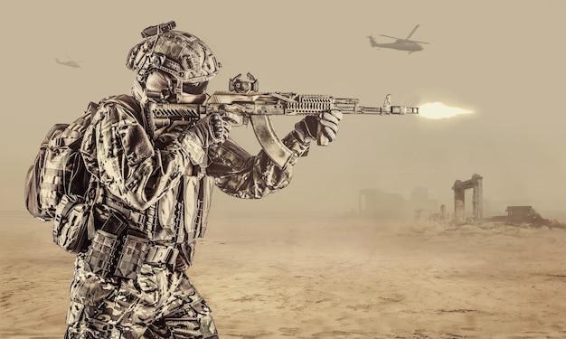 Exploitant van russische speciale operatietroepen met een kalashnikov-aanvalsgeweer, een militaire rugzak en een gevechtshelm die een wapen afschiet in de woestijn in syrië. oude ruïnes en helikopters