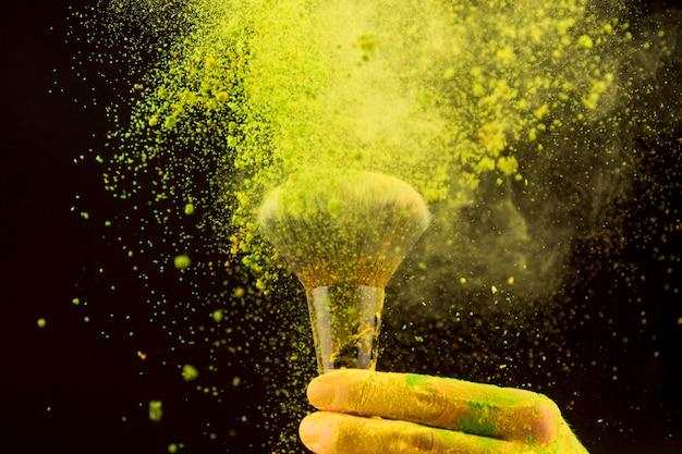 Explosie van geel poeder met make-upborstel op donkere achtergrond