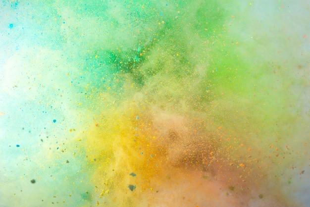 Explosie van gekleurd poeder op een witte achtergrond