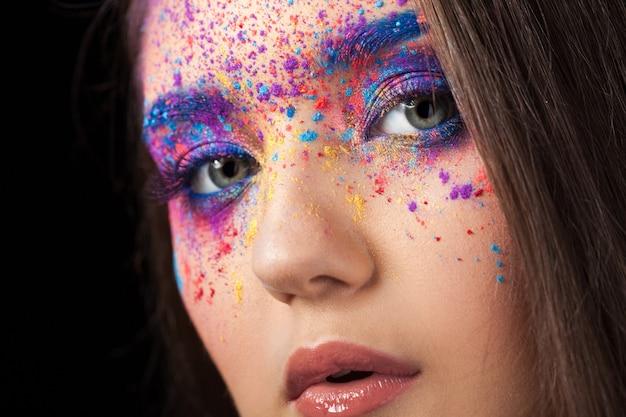 Explosie van kleur, veelkleurige schaduwen verspreid over de oogleden. gekleurde smokey eyes en blauwe wenkbrauwen.