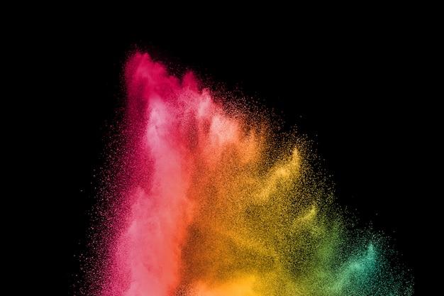 Explosie van kleurenpoeder op zwarte achtergrond. splash van kleur poeder stof op donkere achtergrond.