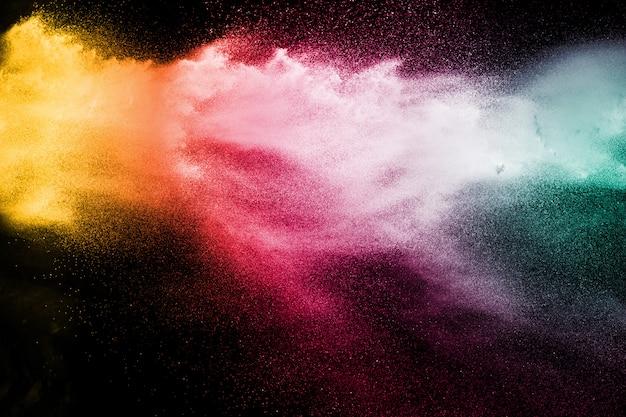 Explosie van kleurenpoeder op zwarte achtergrond.