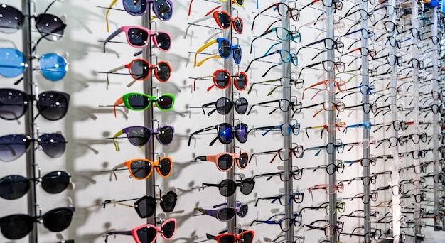 Exposant van brillen bestaande uit planken met modieuze brillen getoond op een muur in de optische winkel