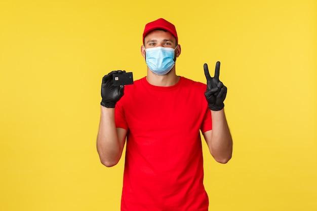 Express levering tijdens pandemie, covid-19, veilige verzending, online winkelconcept. leuke koerier in rood uniform, medisch masker en handschoenen, toon vredesteken en creditcard voor contactloze betaling