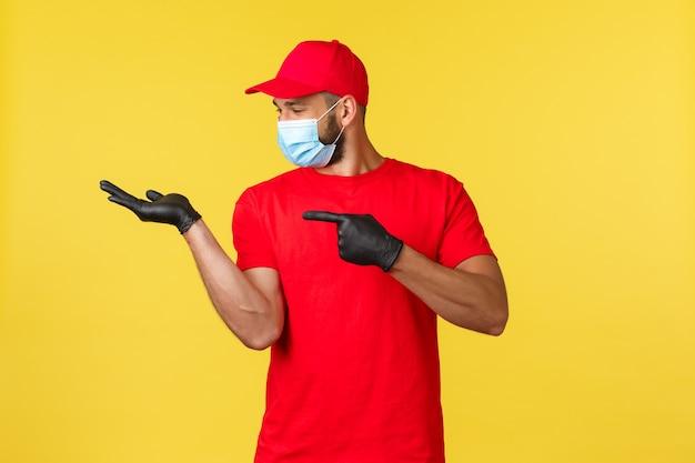 Express levering tijdens pandemie, covid-19, veilige verzending, online winkelconcept. tevreden glimlachende koerier in rood uniform, medisch masker en handschoenen, wijzend naar de hand met product- of promobanner