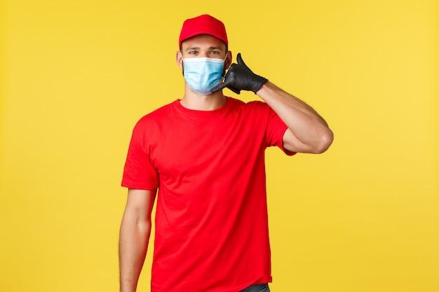 Express levering tijdens pandemie, covid-19, veilige verzending, online winkelconcept. vriendelijke jonge postmedewerker, handler of koerier in rood uniform en medisch masker, vraag om te bellen om te bestellen