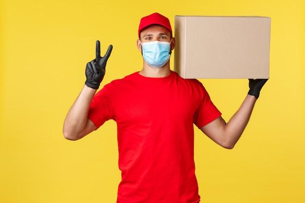 Express levering tijdens pandemie, covid-19, veilige verzending, online winkelconcept. vriendelijke knappe koerier in rood uniform, medisch masker, vredesteken tonen en doospakket vasthouden