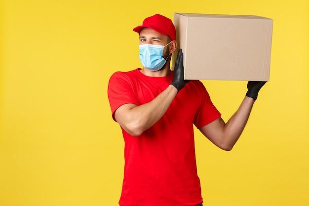 Express levering tijdens pandemie, covid-19, veilige verzending, online winkelconcept. vriendelijke koerier in rood uniform en medisch masker, knipoog, verzorgingspakket, doos op schouder houden