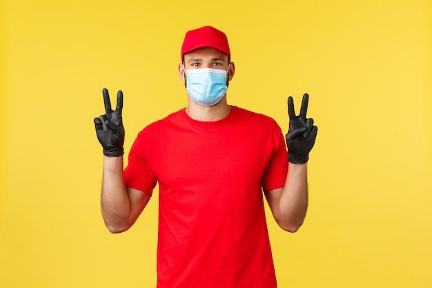 Express levering tijdens pandemie, covid-19, veilige verzending, online winkelconcept. vriendelijke koerier in rood uniform, medisch masker en handschoenen, toon vredesteken, gele achtergrond