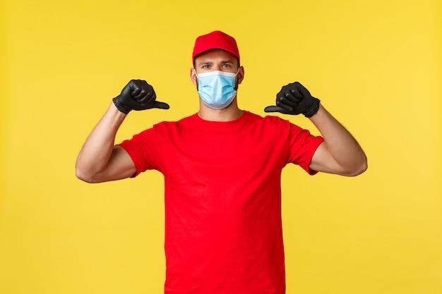 Express levering tijdens pandemie, covid-19, veilige verzending, online winkelconcept. zelfverzekerde en vastberaden koerier in rood uniform, medisch masker, zichzelf serieus wijzend, held bezorgt bestelling