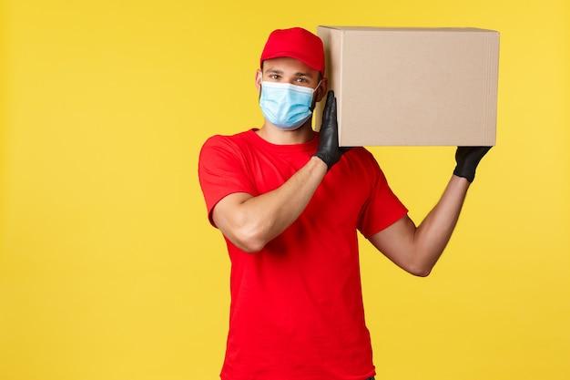 Express levering tijdens pandemie, covid-19, veilige verzending, online winkelconcept. zorgzame knappe koerier die voor uw pakket zorgt, pakket op schouder houdt, doos beschermt, medisch masker draagt