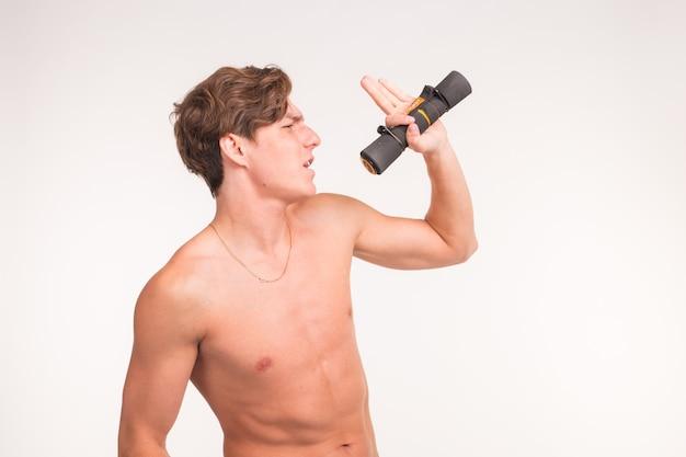 Expressie, fitness en gebaar concept - knappe sportieve man zingen met halter op witte achtergrond met kopie ruimte.
