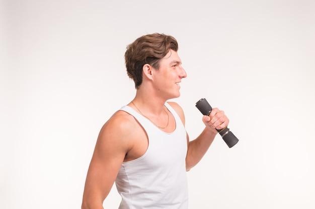 Expressie, fitness en mensen concept - knappe jongen met sport lichaam en halters op witte achtergrond.