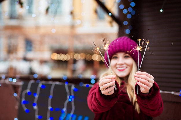 Expressief blond meisje met gloeiende bengaalse lichten op de kerstmarkt in kiev. vervagingseffect