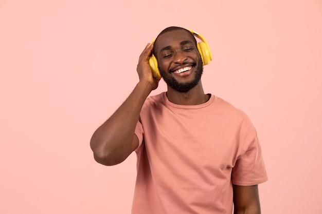 Expressieve afro-amerikaanse man die naar muziek luistert op een koptelefoon