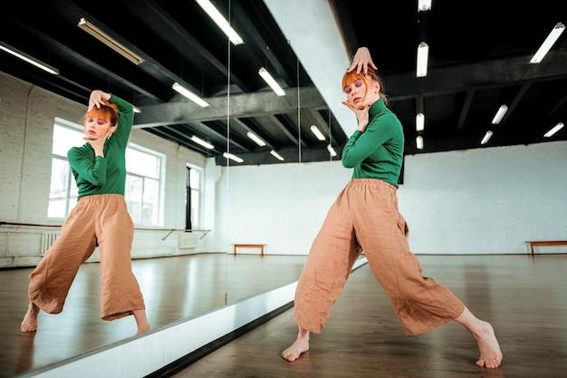 Expressieve bewegingen. mooie professionele moderne danseres met rood haar die er expressief uitzien tijdens het oefenen van dansbewegingen