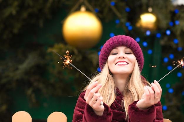 Expressieve blonde vrouw die plezier heeft met sprankelende bengaalse lichten op de nieuwjaarsspar in kiev