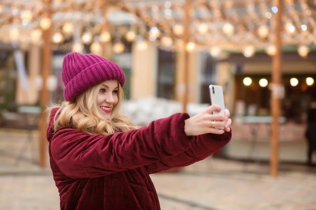 Expressieve blonde vrouw die zelfportret maakt op de mobiele telefoon op de achtergrond van kerstverlichting